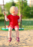 Little girl on a swing in the park. Happy little girl on a swing stock image