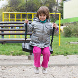 Little girl on swing at playground Stock Photo