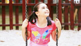 Little girl on swing smiling at camera stock video footage