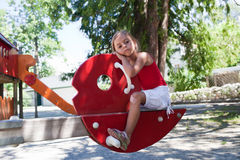 Little girl on swing in summer park Royalty Free Stock Image