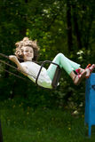 Little girl on a swing in the summer park Stock Image