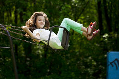 Little girl on a swing in the summer park Stock Photography