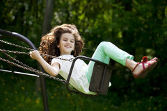 Little girl on a swing in the summer park Royalty Free Stock Image