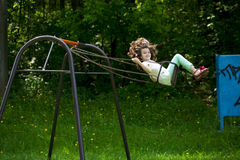 Little girl on a swing in the summer park Stock Images