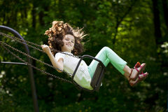 Little girl on a swing in the summer park. Happy Little girl on a swing in the summer park royalty free stock images