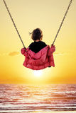 Little girl on the swing. Watching the sunset over the sea royalty free stock images