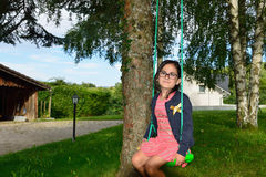 Little girl on swing. Wile eating a cookie royalty free stock photo
