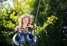 Little girl is swinging Stock Image