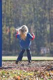 Little Girl Swinging. Child swinging at playground on beautiful fall day, soft breeze blowing her hair Royalty Free Stock Photography