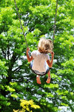 Little girl swinging Royalty Free Stock Images