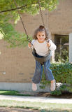 Little Girl Swinging Stock Images