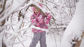 Little girl swinging on the branches of trees, snow-covered stock video