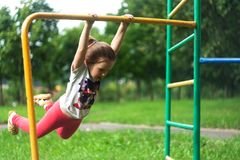 A little girl is swinging on a crossbar. Like a swing. The child is hanging on the bar. She swings like a pendulum. Children`s amateur street gymnastics royalty free stock image