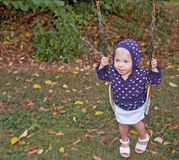 Little Girl Swinging on Fall Day. This little girl wearing a hoodie and sandals is swinging on an autumn day Royalty Free Stock Images