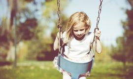 Little Girl Swinging Stock Image