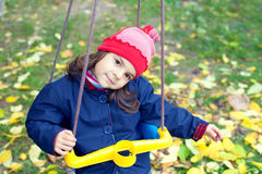 Little girl swinging in the garden Royalty Free Stock Photos