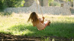 Little girl swinging. Little blonde girl swinging slow motion stock video footage