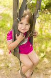 Little girl swinging on a parachute straps Stock Images