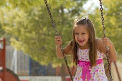Little girl swinging in the park Stock Photos