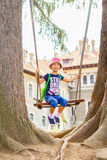 Little girl is swinging at play ground between two old giant fir trees Stock Image