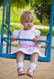 Little girl swinging in a playground. Little girl in dress swinging in a playground Royalty Free Stock Photography