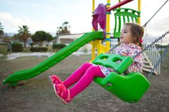 Little Girl Swinging. At Playground Stock Image