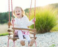 Little girl swinging on a playground. Childhood, Freedom, Happy Summer Concept Stock Photos