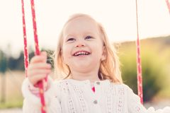 Little girl swinging on a playground. Childhood, Happy, Summer Outdoor Concept. Little girl swinging on a playground. Childhood, Freedom, Happy, Summer Outdoor Royalty Free Stock Photography