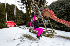 Little girl swinging on playground at cold snowy day Royalty Free Stock Photography