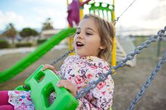 Little Girl Swinging At Playground stock photos