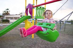 Little Girl Swinging At Playground. Happy Little Girl Is Swinging At Playground Stock Photography