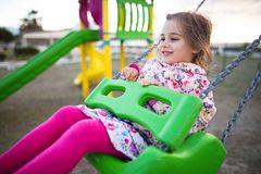 Little Girl Swinging At Playground. Happy Little Girl Is Swinging At Playground Stock Photos