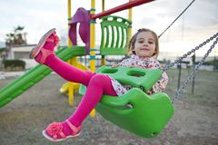 Little Girl Swinging At Playground. Happy Little Girl Is Swinging At Playground Royalty Free Stock Photography