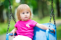 Little girl swinging on playground Royalty Free Stock Image
