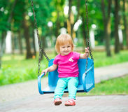 Little girl swinging on playground Stock Images