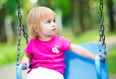 Little girl swinging on playground Stock Photography