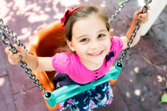 Little Girl Swinging At Playground Outdoors. In Summer stock images