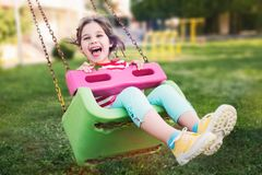 Little Girl Swinging At Playground Outdoors In Summer Stock Images
