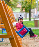 Little girl swinging on seesaw on children playground Stock Photos