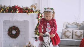A little girl is swinging while sitting on a toy horse in a room with a Christmas decor and a decorated Christmas tree. A little cute girl in a red dress is stock video footage