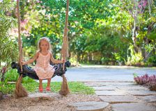 Little girl swinging on a swing in cozy lovely Stock Image