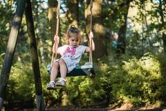 Little girl swinging on a swing. Cute little girl swinging on a swing in the park Stock Image