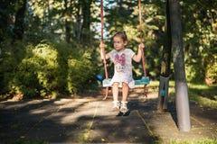 Little girl swinging on a swing. Cute little girl swinging on a swing in the park Royalty Free Stock Image