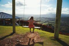 Little girl swinging on a swing. Montana Redonda. Dominican Republic Stock Photo