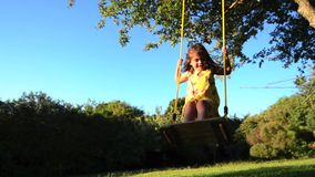 Little girl swinging on a swing stock video