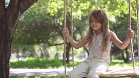 Little girl swinging on a swing in summer Park. swing on ropes attached to the tree. a happy carefree childhood. slow stock video footage