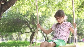 Little girl swinging on a swing in summer Park. swing on ropes attached to the tree. a happy carefree childhood. slow stock video