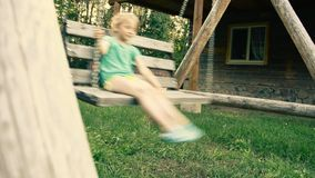 Little girl on the swings. A child plays stock video footage