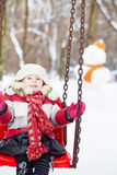 Little girl swings on seat suspended on chains Stock Image