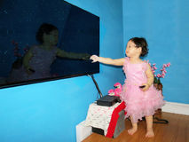 Little girl swiping television screen. A cute little girl standing in front of television swiping screen and holding remote control in the other hand Stock Photos